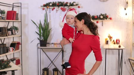 nevinný : Portrait of a beautiful slender mother with a one-year-old child in her arms, the baby is dressed in a red Santa costume with a hat. Happy mom is playing with a newborn baby on Christmas eve.