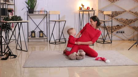 ursinho de pelúcia : Portrait of cute young mom with little baby at home on the floor, they are dressed in red clothes and playing with Teddy bear. Christmas holidays at home. Portrait of mother and baby in suit of Santa.