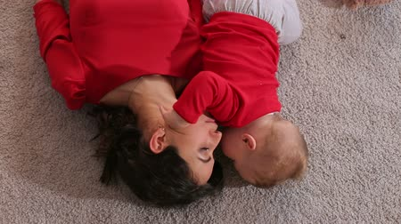 младенец : Top view of the young woman and her little son who lie on the fluffy carpet of the house in the bedroom. Portrait of happy mom with newborn baby at home. Стоковые видеозаписи