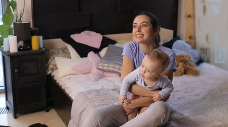 pelenka : Happy little one-year-old child sitting on moms hands in the bedroom on the bed, they are played and funny move their hands. Mom and baby boy in diaper playing in cozy bedroom.