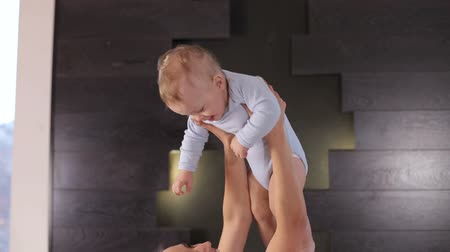 плюшевый мишка : A young mother raises high above the head of her one year old laughing son. Young woman playing with her baby on bed at home. Young mother holding her newborn child. Close-up. Стоковые видеозаписи