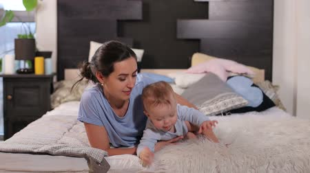 клетчатый : Mom with a small child lying on the bed on a fluffy blanket in the bedroom. Family having fun together. Mom and baby boy in diaper playing in bedroom.