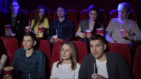 興味深い : Group of teenager friends at the cinema watching a movie together and eating popcorn, entertainment and enjoyment concept. Young people sitting at the cinema.
