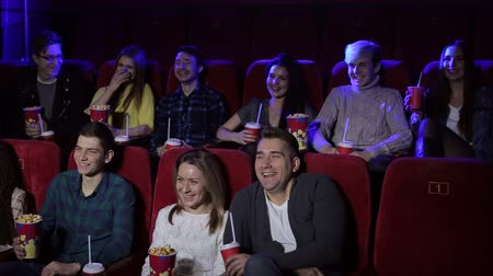 assentos : A group of young people sit in a cinema with popcorn and drinks and watch a funny comedy film, they laugh. Young friends stylish girls and boys watching new movie at cinema, spending time together. Stock Footage