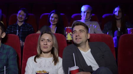 премьера : Happy young couple in love sitting in a movie theater in comfortable red chairs and watching a fun movie. Positive couple drinking cola and eating popcorn in cinema. A cinema full of people.