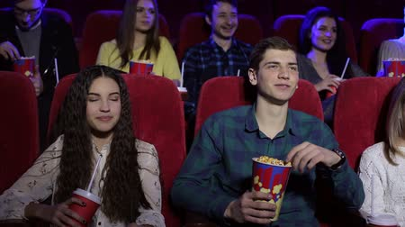 assentos : Close-up of funny teenagers resting in the cinema, they watch Comedy and eat popcorn. Friends watching movie and smiling together, entertainment and enjoyment concept. Stock Footage