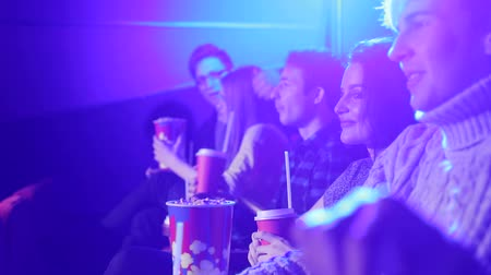 премьера : Close-up view of the cinema with people, a young couple in love and friends of teenagers are watching a movie in a modern cinema. Friends brought food and drinks to the movies. Side view.