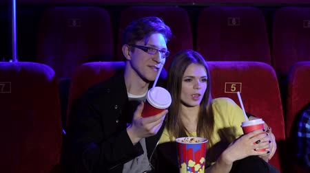 cola : Portrait of a happy couple in love at the cinema, guy with glasses hugging his beloved girlfriend. A couple watching a melodrama, eating popcorn and drinking a cola. Stock Footage