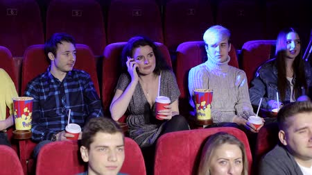 obnoxious : Rude woman talking on phone and disturbing other viewers in cinema. Woman in the theater talking on a cell phone and watch a movie, she disturbing and the man makes her remark.