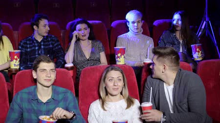 megjegyzés : Rude young woman talking on mobile phone while watching movie at the cinema and disturbing audience. The man turns to her and asks her to turn off the phone. Stock mozgókép