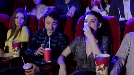 Деятельность выходные : Cheerful young people watch a movie in a modern cinema, a guy drinks his girlfriends drink. Portrait of a group of young people in a cinema with popcorn and Cola. Стоковые видеозаписи
