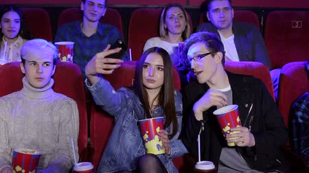 screening : Two friends making selfie in the cinema. Happy gorgeous young girl taking a selfie with her boyfriend while watching a movie together at the cinema. The guy throws popcorn at her and they laugh. Stock Footage