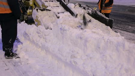 závěj : Workers sweep snow from road in winter, Cleaning road from snow storm. Men workers clean snow from the streets at night. Snowblower cleans the road from snow. Winter. Dostupné videozáznamy