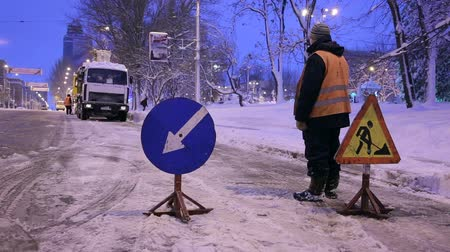 hófúvás : Snowblower clear freezing winter road with snow and ice. Snow-plow remove snow from the city street. Worker install warning road signs. Cleaning snowy frozen roads.