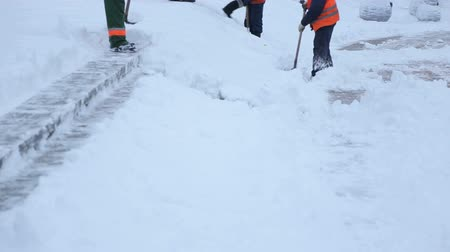 işçiler : Workers with shovels to clear the snow from the stairs in the town square. Workers sweep snow from road in winter, Cleaning road from snow storm. Stok Video