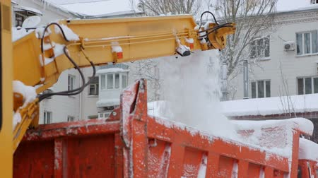 snow plow : Close-up process of working snow plow. Snow plow loads snow into the truck body. City workers clearing snow from the roads after heavy winter snowfalls. Stock Footage