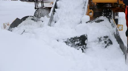 polana : Special transport city cleans the road from snow. Tractor with snowplow equipment removing snow from streets in snow blizzard. Snow plow tractor clearing road during snowstorm.