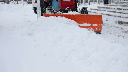 dehet : Backhoe loader scraper snow by claw bucket plow, tractor move backward, then close blades, turn and pour out snow to road side. Removing snow with plow. Dostupné videozáznamy