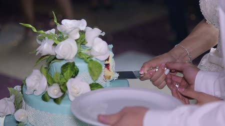 новобрачный : Couple hands cutting wedding cake. The newlyweds cut a beautiful white wedding cake with flowers.