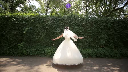 evli : Happy bride spinning in the Park. Brides dress. Wedding day. Happy bride in wedding dress spinning in the Park on the background of green bushes.