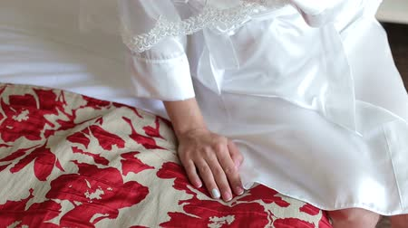 negligee : Close-up of the bride in a satin negligee sitting on the bed with red flowers in the hotel, hand close-up.