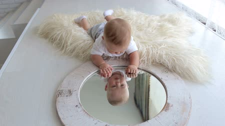 nevinný : A cute little five-month newborn baby is playing with a mirror at home lying on the bed, he sees his reflection and taps his palms on the mirror.