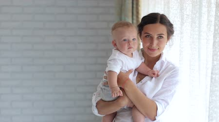 плюшевый мишка : A happy woman holds her little newborn son in her arms and admires him. Portrait of mother and child in the bedroom on the bed. Happy mom plays with her little newborn son at home.