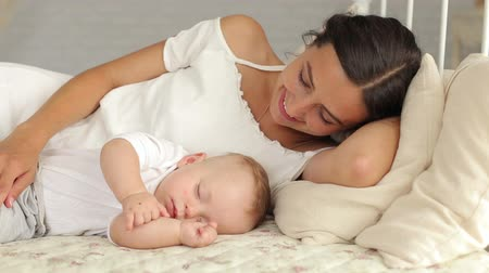 nevinný : Happy mom is lying with her newborn sleeping baby in bed. Mom sleeps next to the baby.