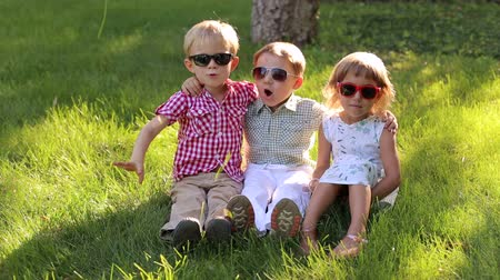 сестры : Three little cheerful children in sunglasses sit on the grass in the Park and laugh.