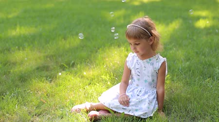 bonitinho : Little girl in summer dress and with hair Hoop sitting on bright green grass in Park, portrait. Summer vacation in nature. Girl with heterochromia. Stock Footage