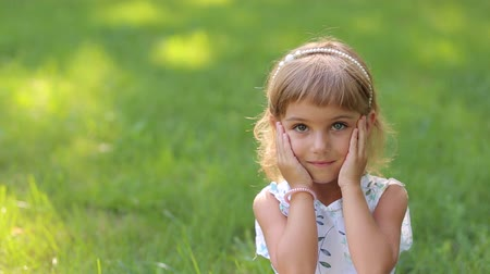 different people : Portrait of cute smiling little girl in Park on green grass background. The view from the top. Heterochromia.