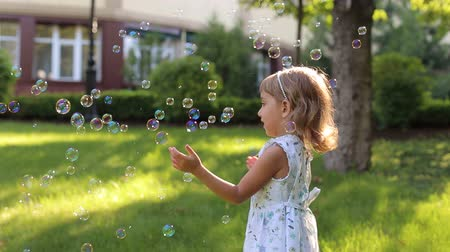 pé : A little cute girl in a summer light dress playing with soap bubbles in the Park on the green grass.