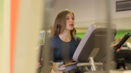 might : Sport girl on orbitrek in the gym. Sport girl run orbitrek gym body fitness concept. Hard cardio workout. Young sporty girl does on the orbitrek at the gym. Stock Footage