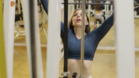 torzo : Strong slender girl doing strength training in the gym among many different simulators. Young brunette works out with hand weights in gym. Strength training. Female fitness. Dostupné videozáznamy