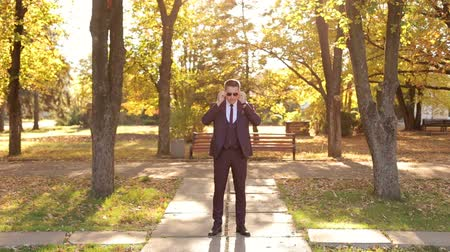 casual wear businessman : Handsome successful businessman in a suit and sunglasses stands in an autumn Park, he adjusts his suit, glasses and tie. Portrait of a confident and successful businessman in the autumn Park at sunset Stock Footage