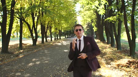 mellow autumn : A successful happy businessman in a suit and sunglasses dancing in the autumn Park enjoying success in business or victory. Winning dance businessman in the autumn Park at sunset. Stock Footage