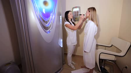 solarium : Portrait of a female cosmetologist with a client in an artificial tanning room, she checks the tanning level with a special device on the girls skin. Professional tanning procedure in the spa salon.