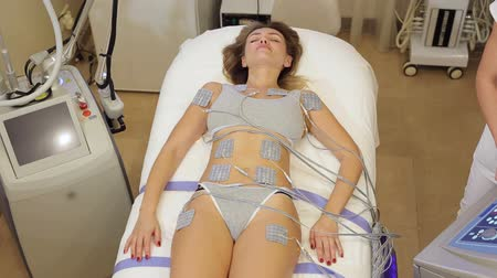 prosedür : A young woman lies in a cosmetic clinic on the couch and receives a biostimulating anti-cellulite body massage. Skin Care concept. Woman getting getting electro stimulation therapy to her body.