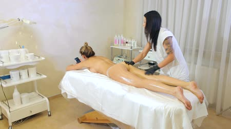 анти : A young girl beautician does a massage to a woman, she rubs her legs with oil. Anti-cellulite massage in the spa salon. Стоковые видеозаписи