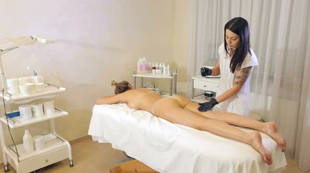 массаж : Sexy girl lying on the massage table in the spa salon. A female masseur does an anti-cellulite massage to a girl in a beauty parlor.