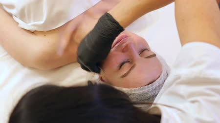 procedure : Close-up beautician in black gloves wipe face with a cotton swab micellar water. Girl on facial rejuvenation procedures in the Spa. Filmati Stock