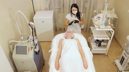 mezoterapia : A woman cosmetologist works with a client in a Spa salon, she splashes a moisturizing liquid on her skin and makes non-injection mesotherapy. Needle mesotherapy. Wideo