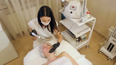 mezoterapia : Close-up portrait of a beautician girl who works with a client in a Spa salon. The view from the top. The process of rejuvenating procedures with hyaluronic acid in a cosmetic clinic. Wideo