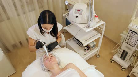 mezoterapia : A young woman enjoys a mesotherapy procedure in a Spa salon, she lies on a cosmetology table with her eyes closed and covered with a towel. Facial massage in the beauty salon.