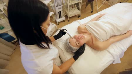 mezoterapia : Cosmetology mesotherapy for facial rejuvenation. The process of non-injection mesotherapy in the Spa. Cosmetologist doing microneedle to a young girl in the beauty salon close-up.