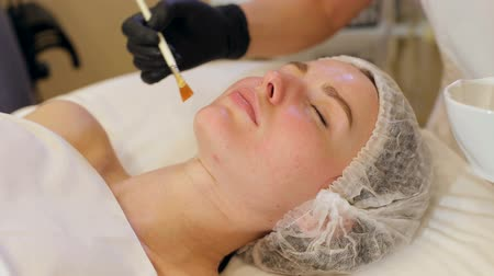 средний возраст : Cosmetologist applies hydrogel on the face of a young woman in a Spa salon. The procedure of moisturizing and rejuvenating the face in cosmetology, close-up. Non-injection mesotherapy.