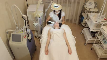 collagen : Doctor with Ultrasonic scrubber doing procedure of ultrasonic cleaning of face. Cosmetological clinic. Healthcare, clinic, cosmetology. Young pretty woman receiving treatments in beauty salons.