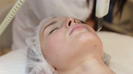 soyulması : Close-up of the girl enjoying the procedure of ultrasonic cleaning of the face in a cosmetic clinic. Hardware cosmetology. Modern skin care.