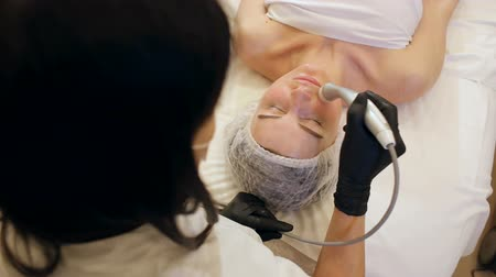 ortalama : Top view of the procedure of non-injection mesotherapy for a young girl in the Spa salon. The beautician does modern anti-aging treatments to the trendy girl. Stok Video