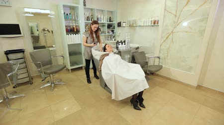 nourishing : Master hairdresser woman applies a mask or oil on the hair of the client. Spa concept recovery. Nourishing oil, hair mask. Hair care Spa. Stock Footage